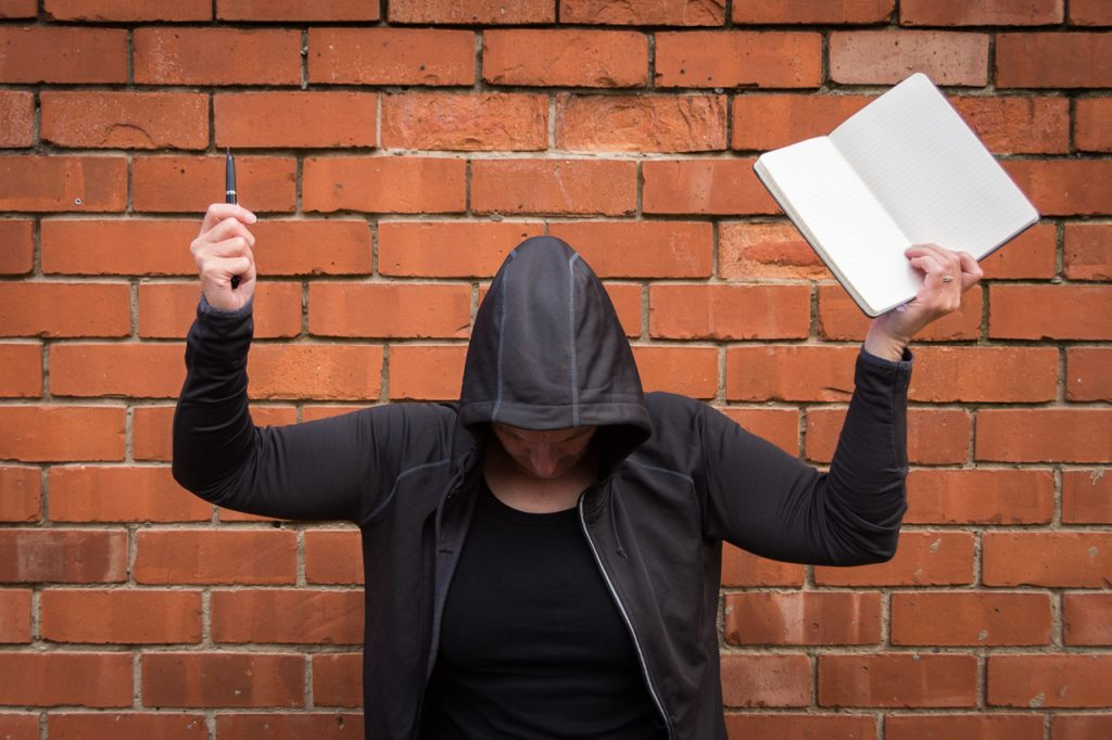 Use your writing muscle - writer wearing a hoodie, holding pen and note-book