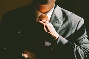 Man in a suit tightening his tie